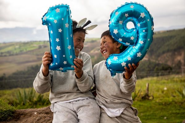 Two childring in grey jogging suits hold balloons shaped like the number 19. They sit in front of a green mountainous landscape and laugh at each other.